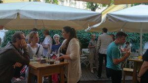 Foto: sitzende und stehende Menschen beim Essen, Trinken und Sprechen im Garten