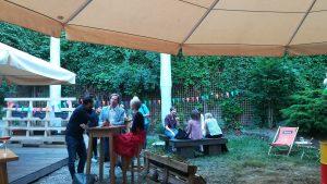 Foto: angeregt sprechende Menschen im bunt geschmückten Garten