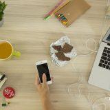 Foto eines Arbeitsplatzes mit Laptop, Handy, Schokolade und Tee
