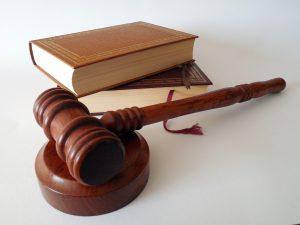 Foto: Ein Holzhammer, wie er beim amerikanischen Gericht verwendet wird, und zwei Bücher.