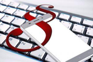 Bild: Eine Computer-Tastatur und ein Smartphone mit Paragraphen-Symbol