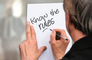 """Foto: Blick über die Schulter eines seriösen Mannes, der """"Know the Rules"""" auf ein Papier schreibt."""