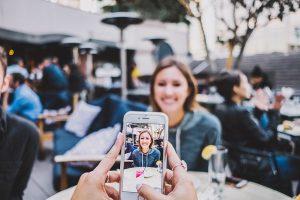 Foto: Zwei Menschen sitzen sich in einem Kaffee gegenüber. Der eine macht ein Foto der ihm gegenüber sitzenden Frau mit seinem Smartphone.