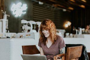 Foto: Junge Frau mit roten Haaren sitzt mit ihrem Laptop in einem Café und surft im Internet.