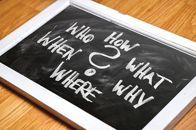 Foto: Holztafel mit geschriebenen Fragen, die man sich bei Newsletter-Umfragen stellen kann: How, What, Why, Where, When, Who?