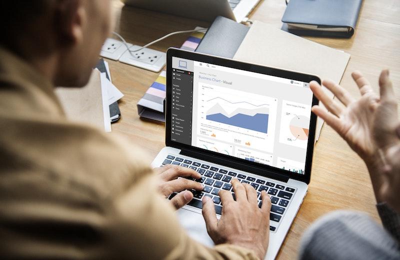Einer Person sieht sich Statistiken an einem Laptop an.