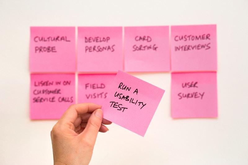 """Eine Wand mit Post-Its. Auf einem Zettel in der Hand einer Person steth """"Run a Usability Test""""."""