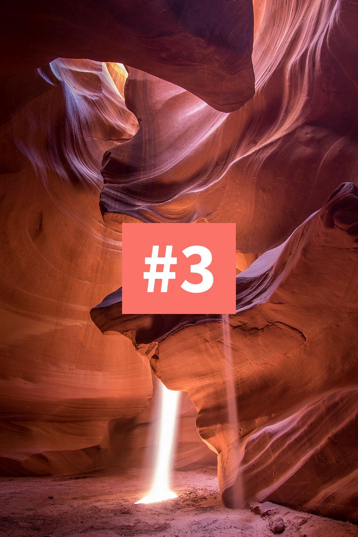 Foto: Eine Höhle in einer Wüste, durch die ein Lichtstrahl von oben dringt.