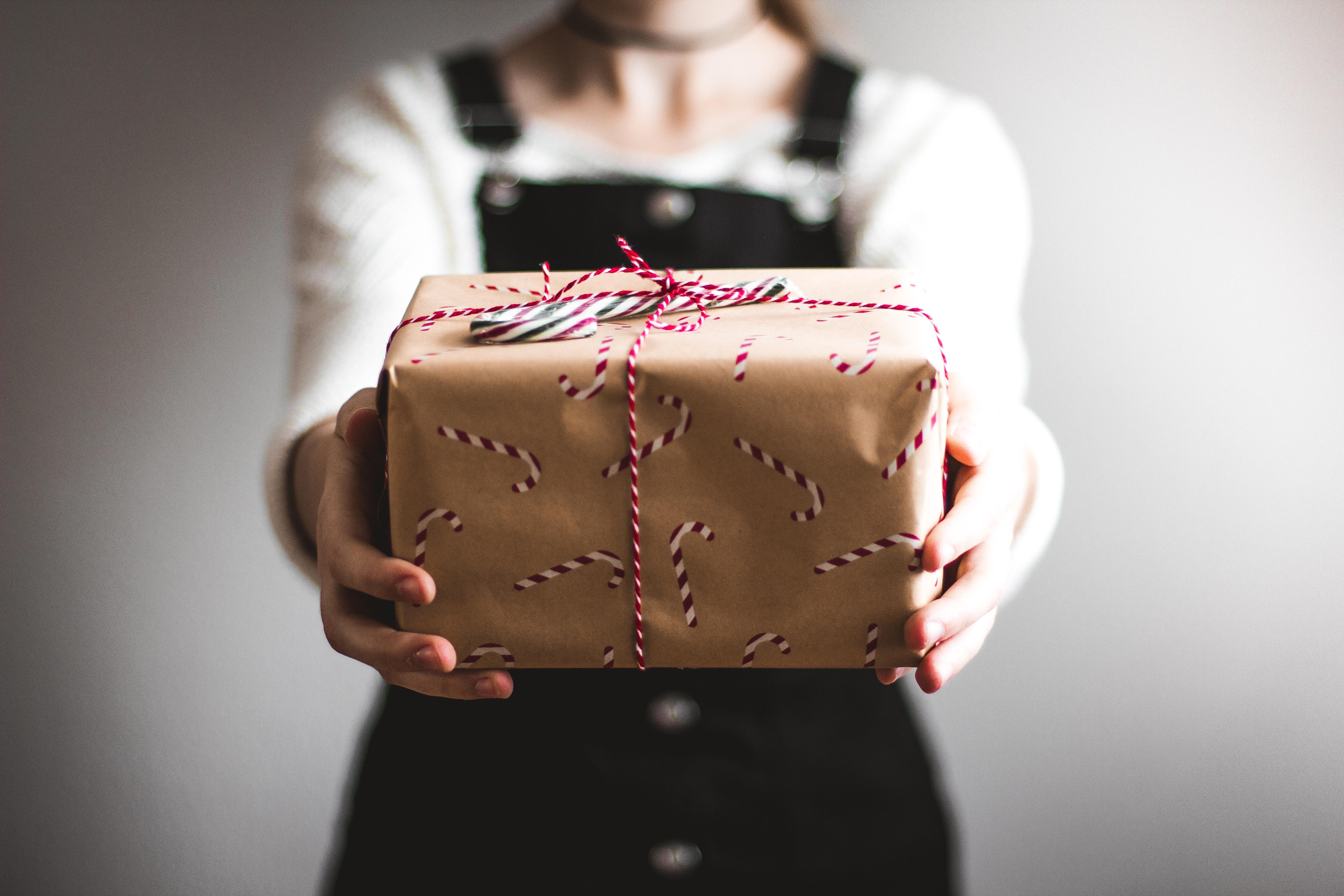 Das Bild zeigt eine Person die ein Geschenk in Richtung Kamera streckt.