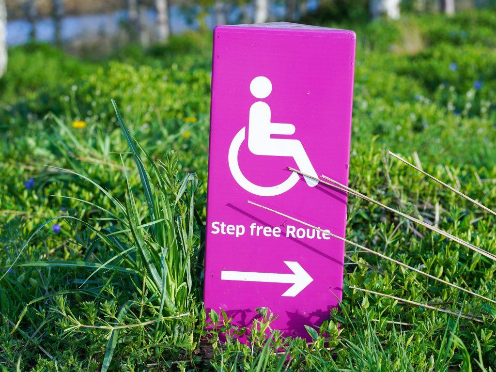 """Auf dem Bild ist ein Schild mit einem Rollstuhl und der Aufschrift """"Step free Route"""" zu sehen."""