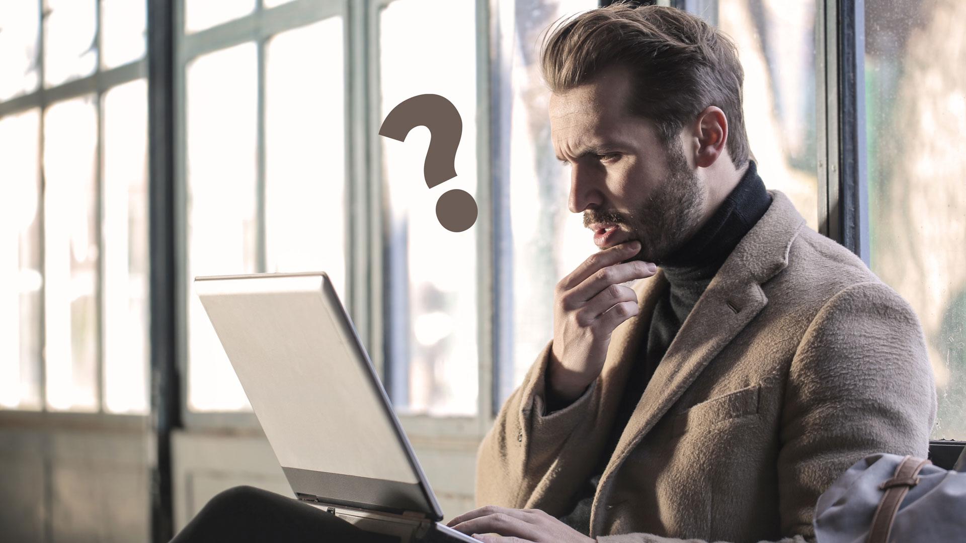 Mann starrt verwirrt auf einen Laptop
