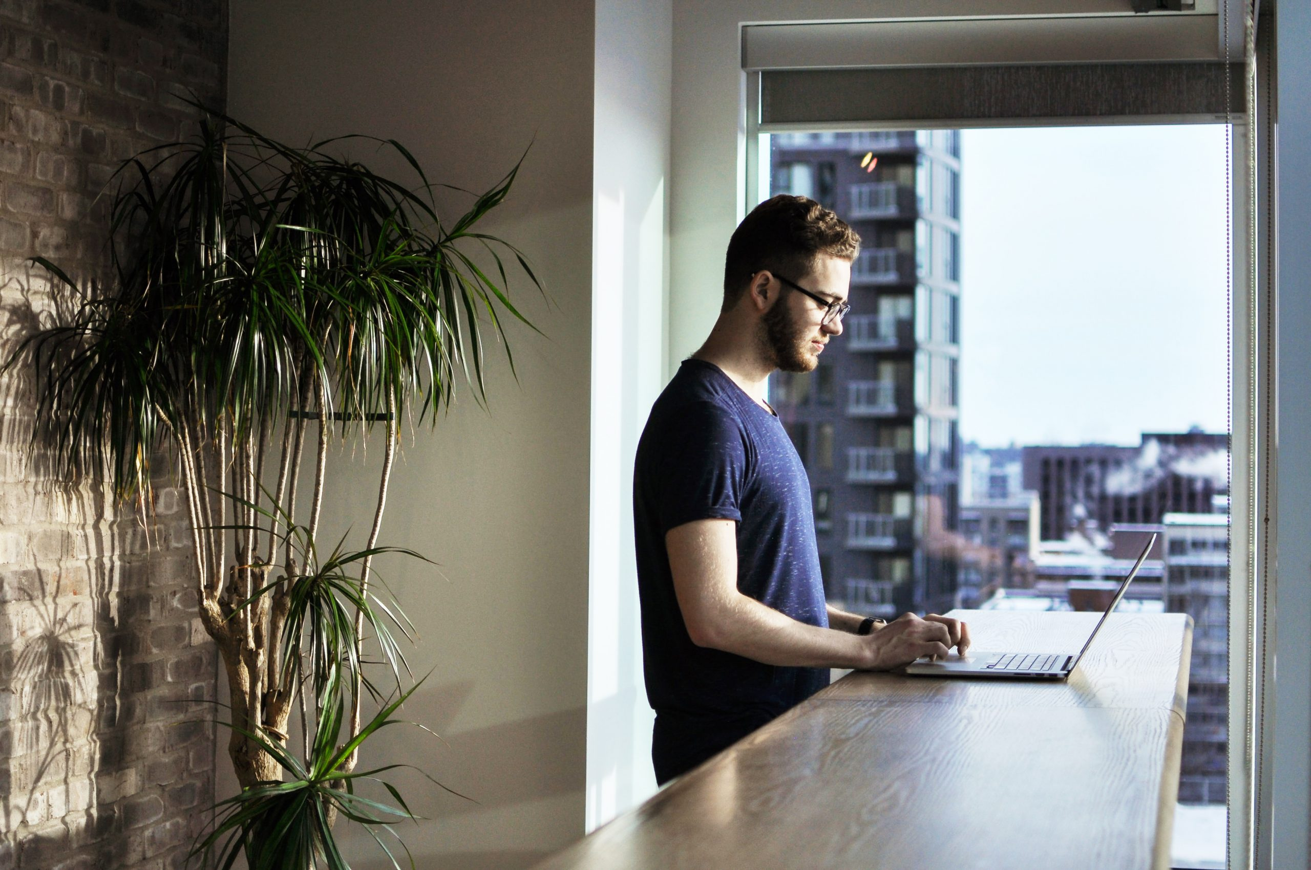 man in front of standing desk using a laptop