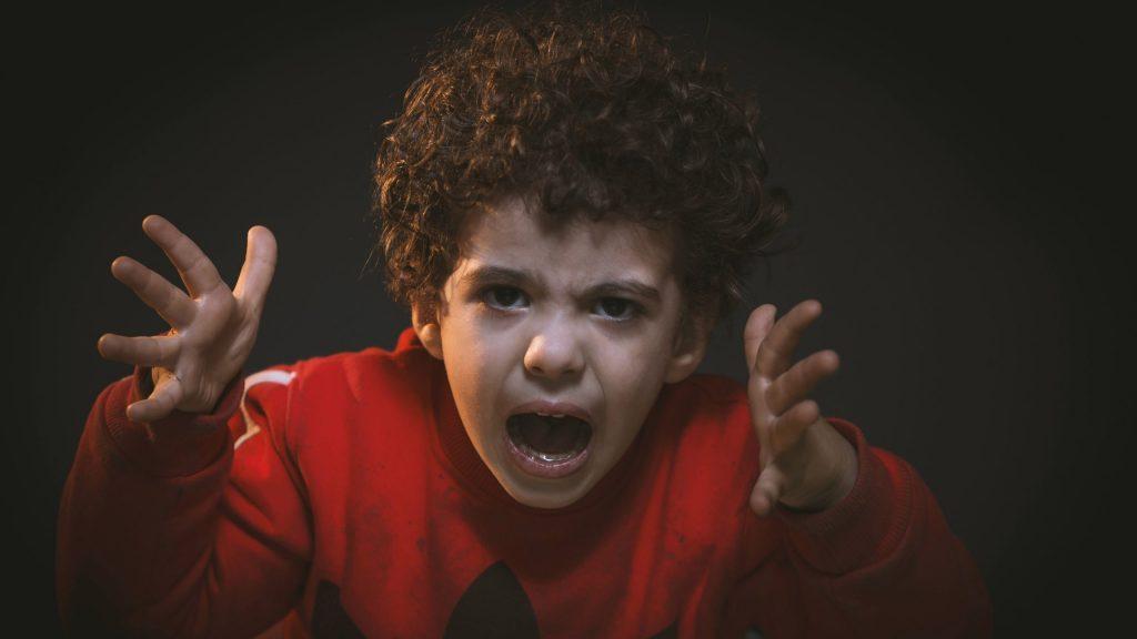 Junge in rotem Shirt schaut wütend in die Kamera