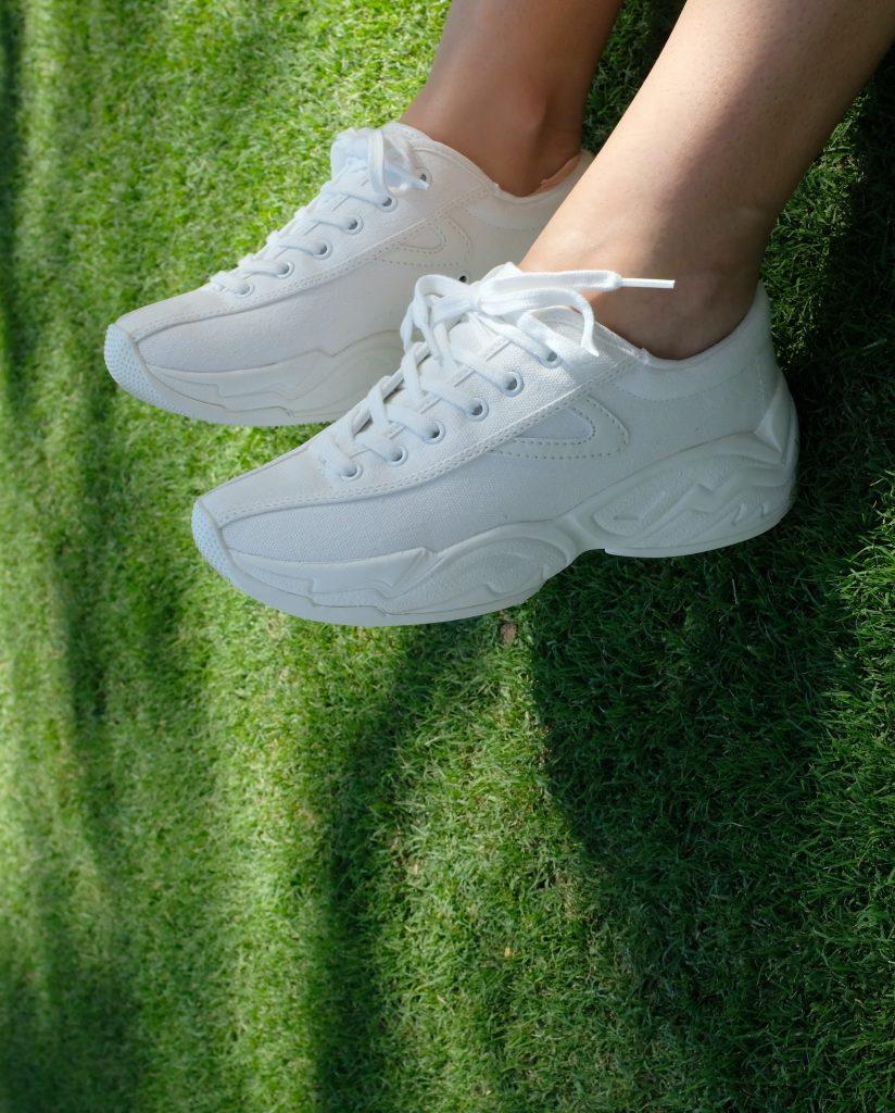 weiße Turnschuhe auf grasgrünem Hintergrund